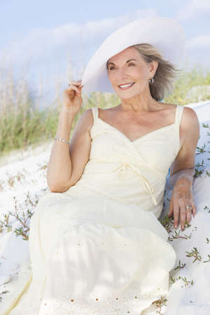An attractive elegant classy senior woman in a yellow sun dress & white sun hat sitting on a white sand beach with grass and a blue sky behind her. Stock Photo - 17862043