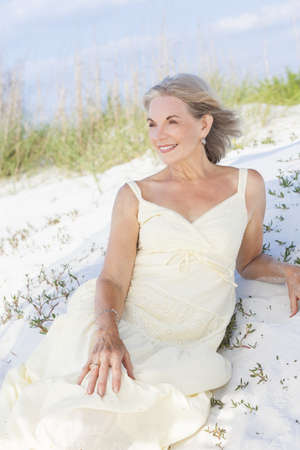 An attractive elegant classy senior woman in a yellow sun dress sitting on a white sand beach with grass and a blue sky behind her. Stock Photo - 17862045