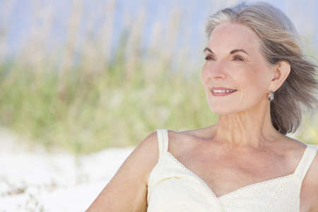 An attractive elegant classy senior woman in a yellow sun dress sitting on a white sand beach with grass and a blue sky behind her. Stock Photo - 17862044