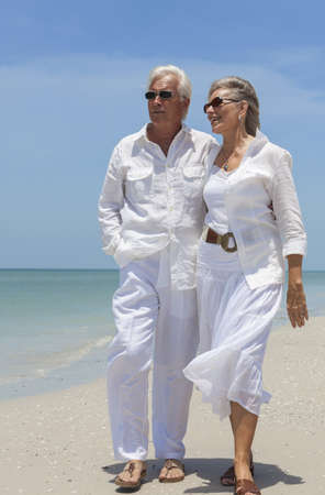 Happy senior man and woman couple together looking out to sea on a deserted tropical beach with bright clear blue sky.