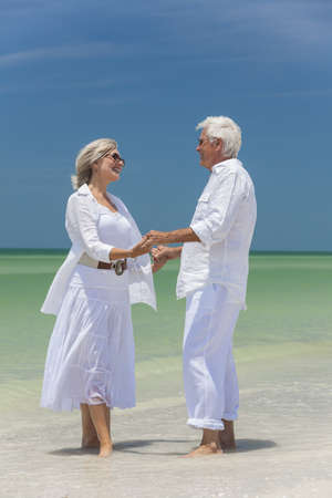 Happy senior man and woman couple together holding hands by sea on a deserted tropical beach with bright clear blue sky Stock Photo - 17862050
