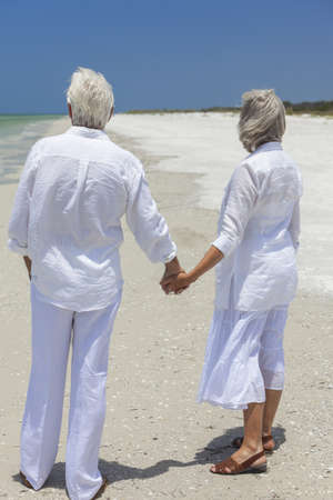 Rear view of happy senior man and woman couple holding hands together looking out to sea on a deserted tropical beach with bright clear blue sky. Stock Photo - 17862051