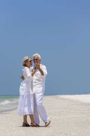Happy senior man and woman couple together dancing by the sea on a deserted tropical beach with bright clear blue sky Stock Photo - 17862052