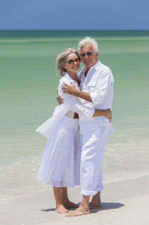 Happy senior man and woman couple together embracing by sea on a deserted tropical beach with bright clear blue sky Stock Photo - 17862049
