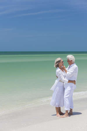 Happy senior man and woman couple together embracing by sea on a deserted tropical beach with bright clear blue sky Stock Photo - 17862047