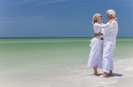 Happy senior man and woman couple together embracing by sea on a deserted tropical beach with bright clear blue sky