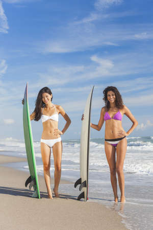 Beautiful young women surfer girls in bikinis with surfboards on a beach Stock Photo - 18315335