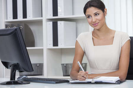 Beautiful young Latina Hispanic woman or businesswoman sitting at a desk in an office writing in her diary photo