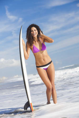 Beautiful young woman surfer girl in bikini with surfboard standing in the surf on a beach