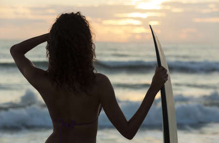 Rear view of beautiful sexy young woman surfer girl in bikini with white surfboard on a beach at sunset or sunrise Stock Photo - 17998478