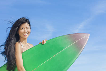 Beautiful young Asian Hawaiian woman surfer girl in bikini with surfboard standing on a beach with blue sky  photo