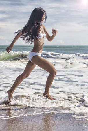 A sexy young brunette Asian woman or girl wearing a white bikini running on a deserted tropical beach with a blue sky  Stock Photo - 18316804