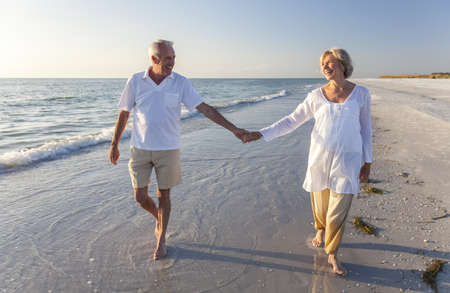 Happy senior man and woman couple walking and holding hands on a deserted tropical beach with bright clear blue sky Standard-Bild