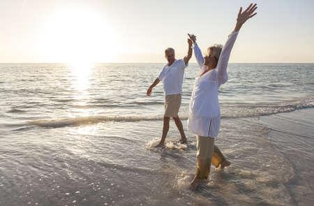 Gelukkig senior man en vrouw paar dansen en hand in hand op een verlaten tropisch strand bij zonsopgang of zonsondergang