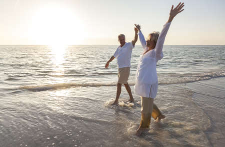 aging woman: Happy senior man and woman couple dancing and holding hands on a deserted tropical beach at sunrise or sunset