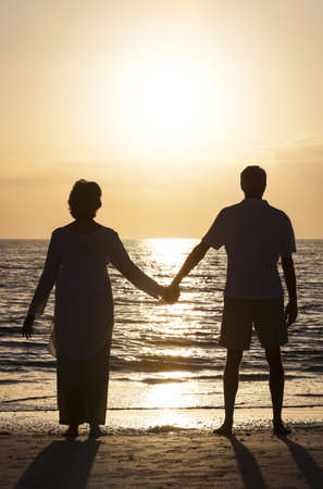 Senior man and woman couple holding hands at sunset or sunrise on a deserted tropical beach  Stock Photo - 18291751