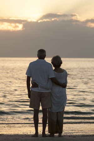 Senior man and woman couple embracing at sunset or sunrise on a deserted tropical beach  Stock Photo