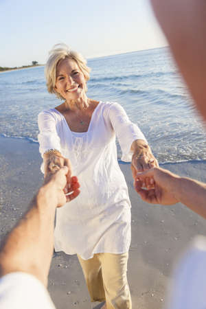 Happy senior man and woman couple dancing and holding hands on a deserted tropical beach with bright clear blue sky Stock Photo - 18316828