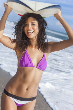 Mooie jonge vrouw surfer meisje in bikini met surfplank op haar hoofd staan in de branding op een strand