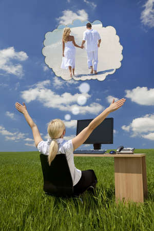 Business concept shot of a beautiful young woman sitting at a desk using a computer in a green field raising her arms into the sky daydreaming of being on a tropical beach with her husband or boyfriend photo