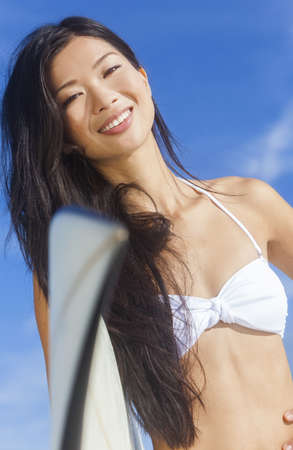 Beautiful young Hawaiian Asian woman surfer girl in bikini with surfboard standing in the surf on a beach  Stock Photo - 19285158