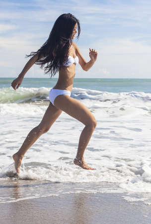 A sexy young brunette Asian woman or girl wearing a white bikini running on a deserted tropical beach with a blue sky  photo