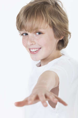 White background studio photograph of young blond boy smiling and reaching to the camera  Stock Photo - 19285163