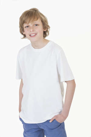 White background studio photograph of young happy boy smiling hands in pockets wearing blue denim jeans and white T-shirt Stock Photo - 19285146