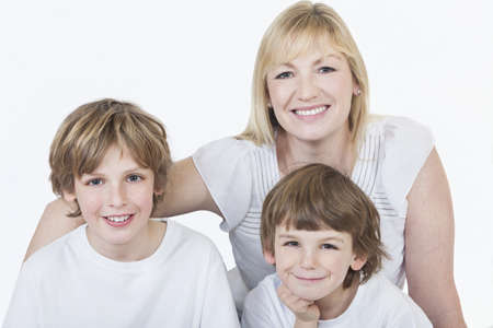 White background studio photograph of young happy family mother and two boy sons smiling Stock Photo - 19285151