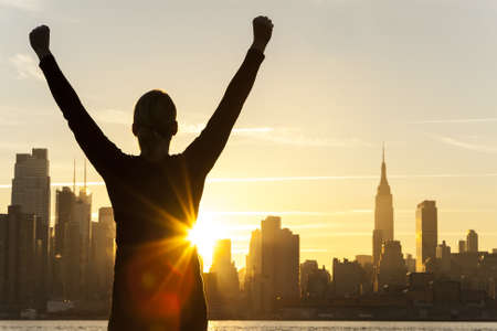 Silhouette of a successful woman or girl arms raised celebrating at sunrise or sunset in front of the New York City Skyline Stock Photo - 19285145