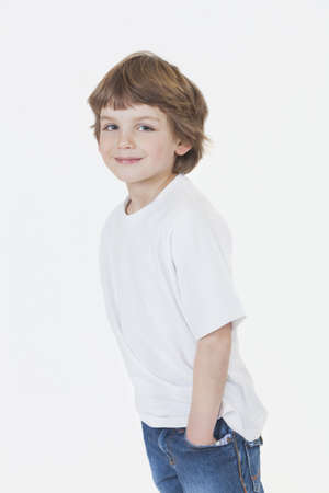 White background studio photograph of young happy boy smiling hands in pockets wearing blue denim jeans and white T-shirt Stock Photo - 19285150