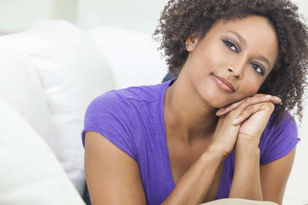 A beautiful mixed race African American girl or young woman looking happy and thoughtful Stock Photo - 19285157