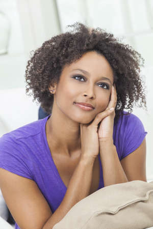 A beautiful mixed race African American girl or young woman looking happy and thoughtful Stock Photo - 19285161