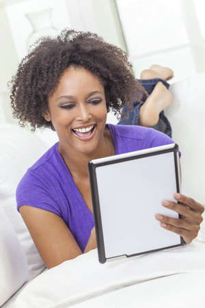 A beautiful happy mixed race African American girl or young woman laying down on sofa using a tablet computer Stock Photo - 19285154