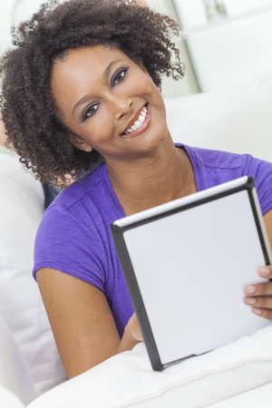 american sexy: Красивая счастливым смешанной расы афро-американских девушка или молодая женщина, устанавливающий на диване с помощью планшетного компьютера