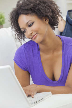 A beautiful happy mixed race African American girl or young woman laying down on sofa using a laptop computer Stock Photo - 19285131