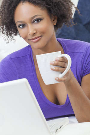 A beautiful happy mixed race African American girl or young woman laying down on sofa using a laptop computer and drinking tea or coffee Stock Photo - 19285159