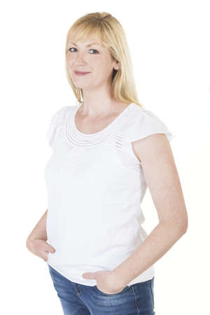 Isolated white background studio photograph of happy smiling middle aged blond woman in blue denim jeans and white shirt photo