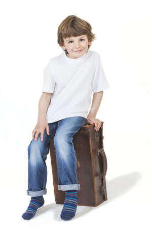 White background studio photograph of young happy boy smiling and sitting on a suitcase ready for vacation traveling Stock Photo - 19406932