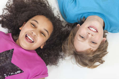 Overhead photograph of two children, blond boy and mixed race African American girl, having fun laying down and laughing Stock Photo - 19406928