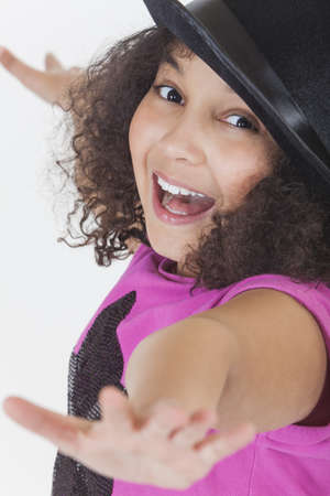 Studio shot of a beautiful happy young mixed race girl laughing and singing wearing a black top hat Stock Photo - 19406926