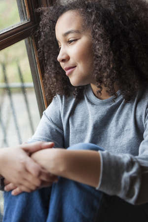 Beautiful young mixed race African American girl sitting smiling and looking out of a rain covered window Stock Photo - 19406927