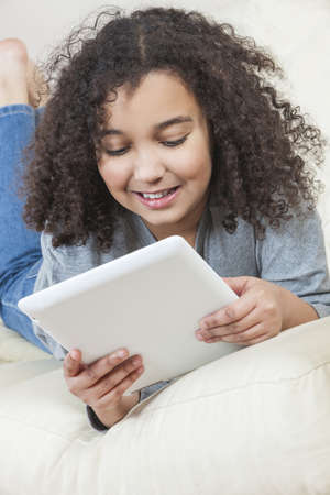 Beautiful happy young mixed race African American girl smiling and using a tablet computer at home on her sofa Stock Photo - 19406929