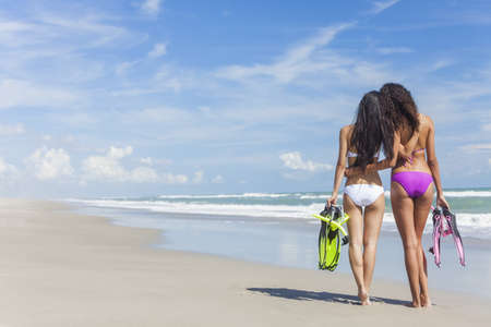 flippers: Rear view of two beautiful young women in bikinis with snorkel, mask & flippers embracing on a deserted beach with blue sky