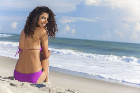 woman back view: A sexy young brunette woman or girl wearing a bikini sitting on a deserted tropical beach with a blue sky  Stock Photo