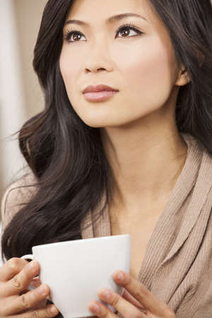 A beautiful young Chinese Asian Oriental woman drinking tea or coffee from a white cup photo