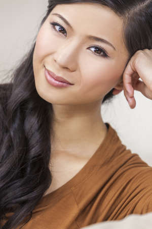 Portrait of a beautiful young Chinese Asian Oriental woman resting on her hand photo