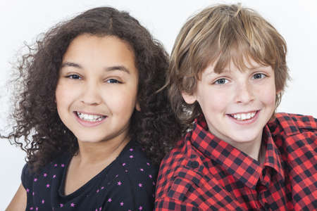 Two children, blond boy and mixed race African American girl, having fun smiling white background studio shot photo