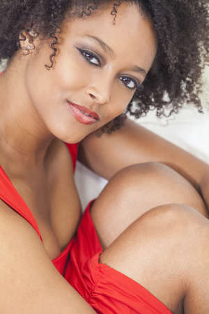 A beautiful sexy mixed race African American girl or young woman wearing a red dress looking happy and smiling