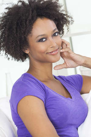 A beautiful mixed race African American girl or young woman looking happy and thoughtful Stock Photo - 19587672